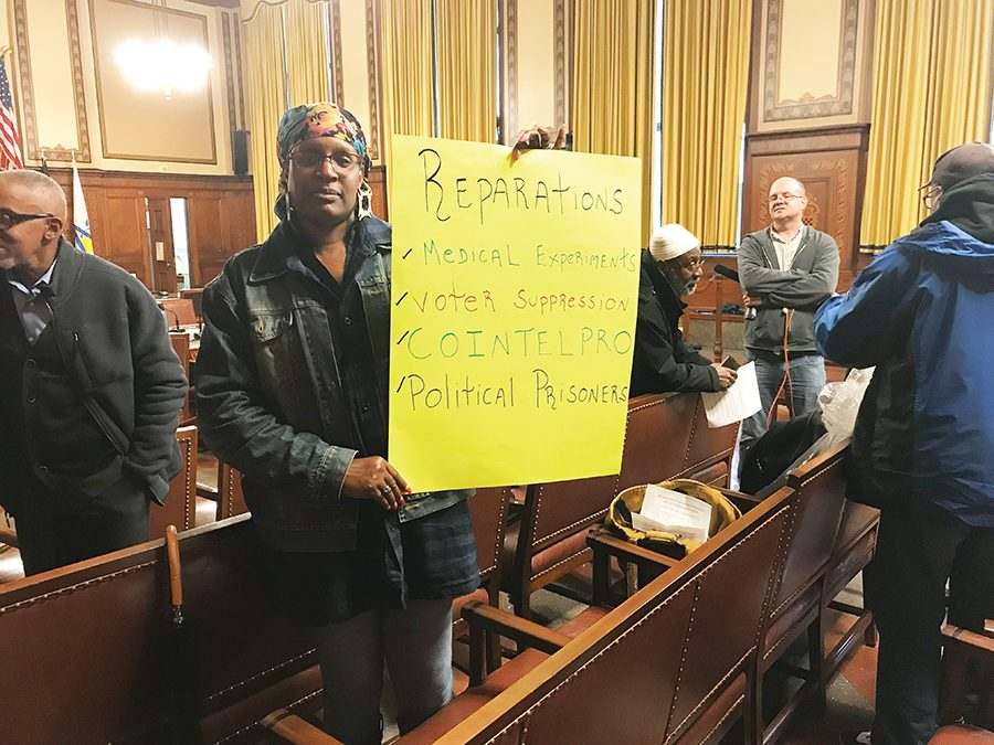 A woman standing with a poster after the public hearing concluded. Causes for reparations were extensively discussed by speakers.