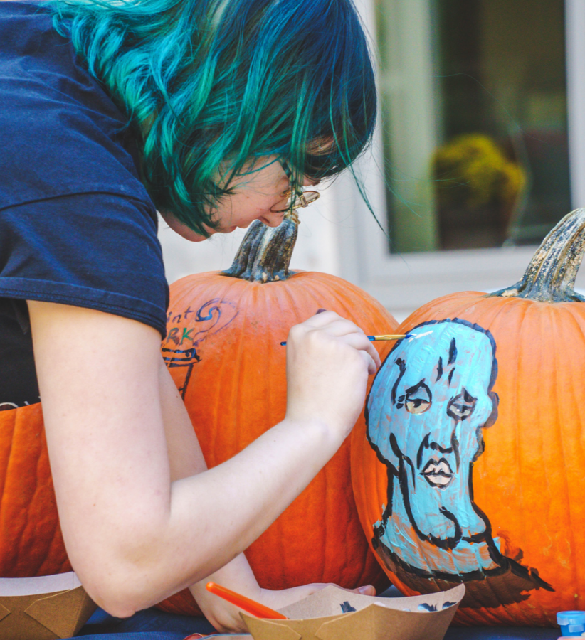 Freshman information technology major Maddie Mitchell paints Handsome Squidward on a pumpkin during CAB's Pittsburgh Pumpkin Patch event in Village Park on Oct. 14.