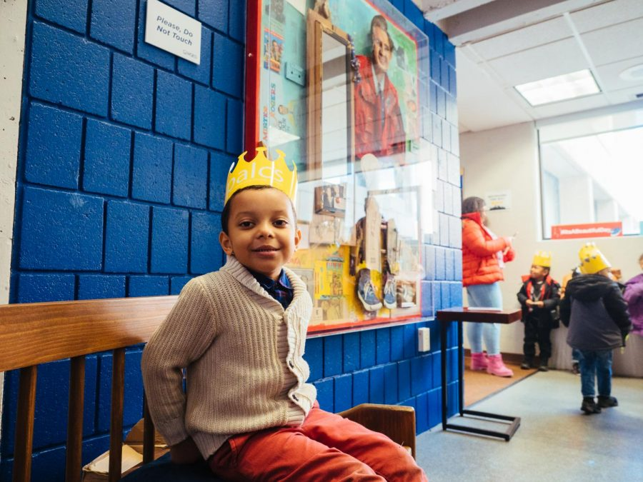 Royal Rodriguez of the Hosanna House sits in front of a mixed media portrait of Mr. Rogers during Cardigan Day at WQED as a part of World Kindness Day.