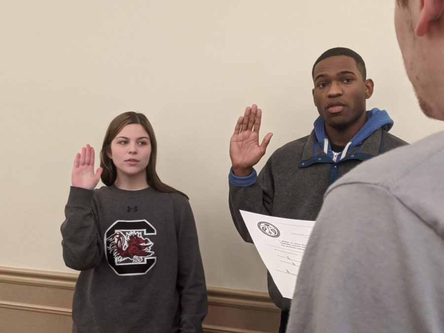 Lillian Hinckley (left) of the School of Arts and Sciences and Chris Blount (right) of COPA are sworn in as senators at Monday's SGA meeting.