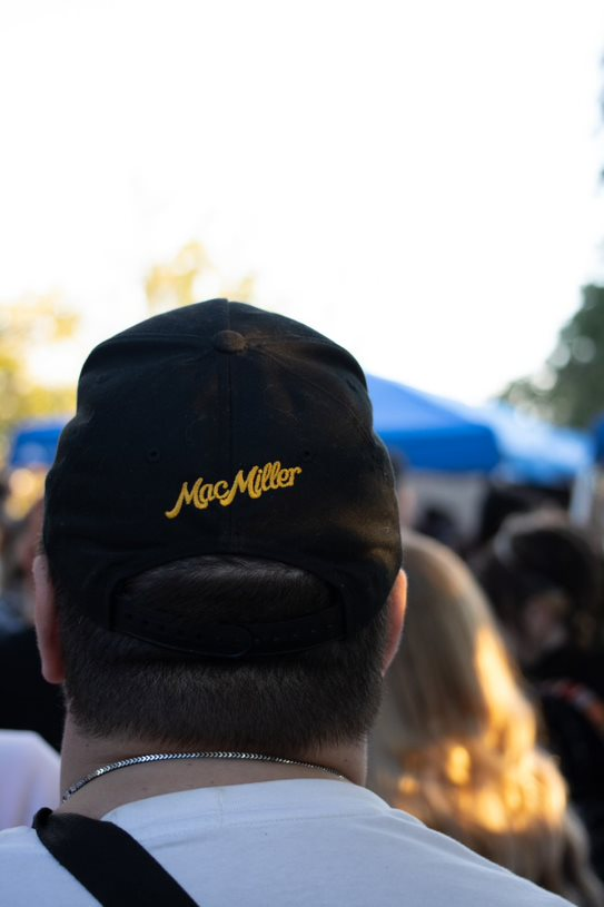 A man wears a cap with Mac Miller's name on it.