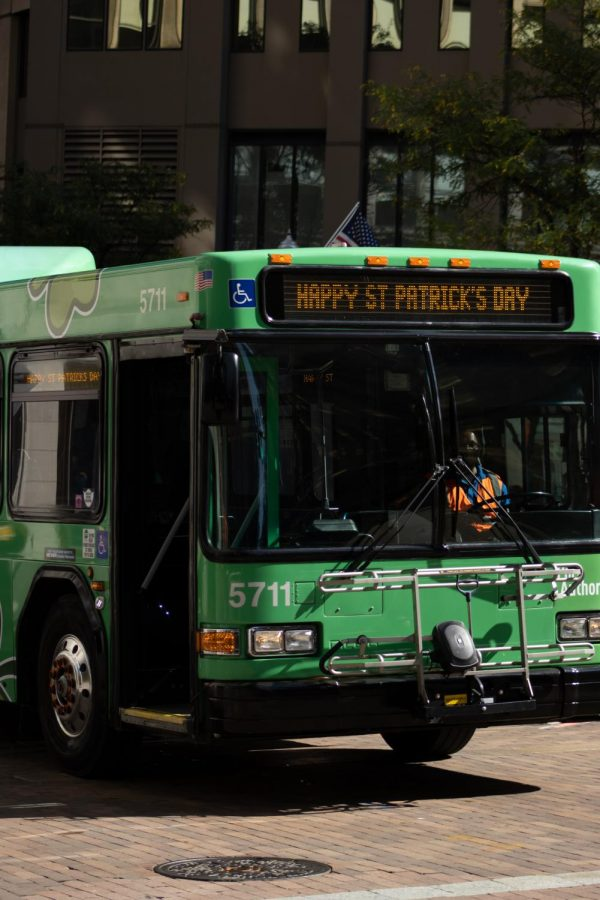 """A Port Authority bus drives down the street in the parade, with a """"Happy St. Patrick's Day"""" banner."""